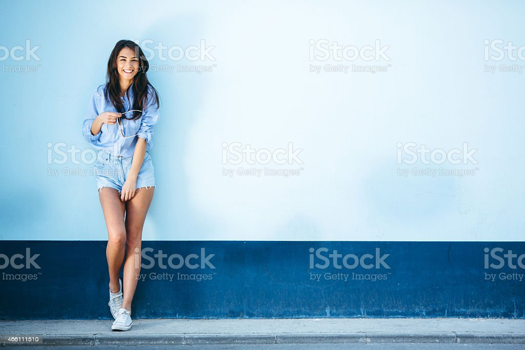 Young beautiful female standing against the wall