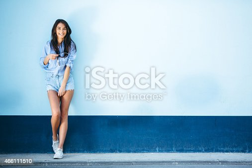 Beautiful female fashion model standing and looking at camera.