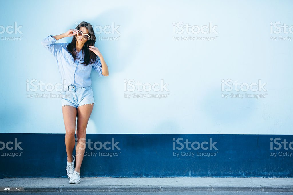 Young beautiful female standing against the wall stock photo