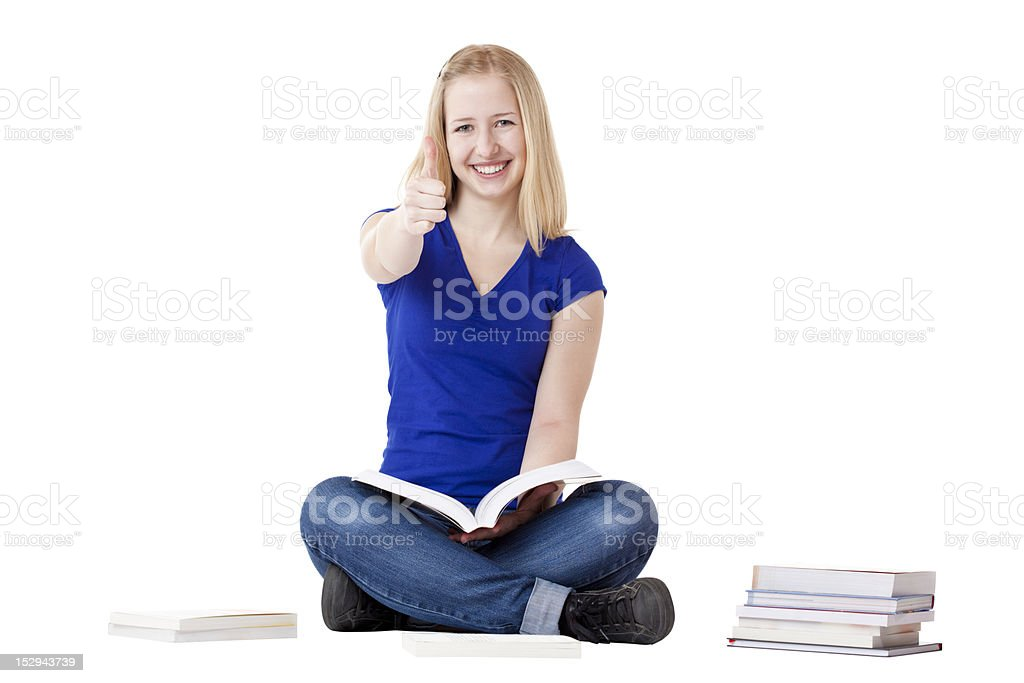 Young beautiful female student sitting on floor showing thumb up stock photo