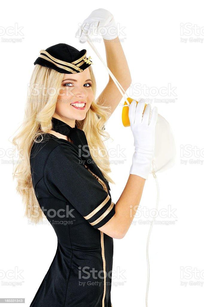Young beautiful flight attendant safety demonstration stock photo