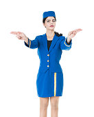 Young Beautiful Flight Attendant Stewardess how showing the extits. Wearing blue uniform and isolated on white.