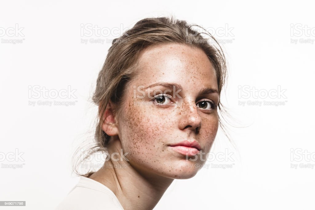 Young beautiful freckles woman face portrait with healthy skin stock photo