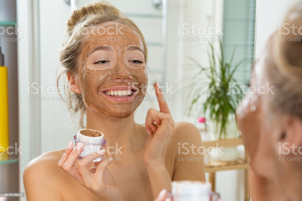Young beautiful girl applying facial scrub mask on skin. stock photo
