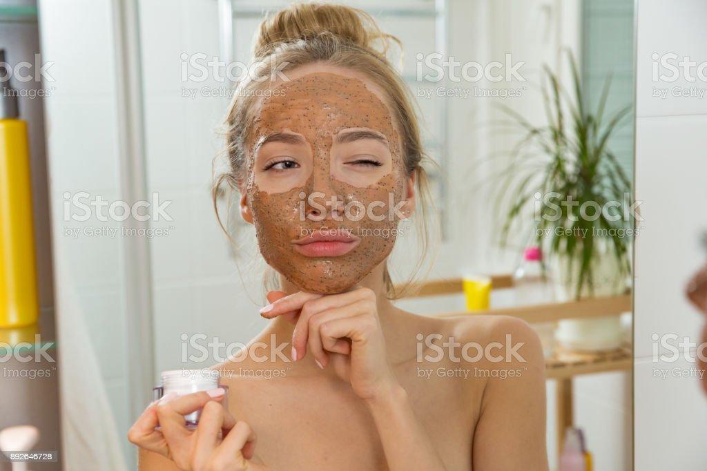 Young beautiful girl applying facial scrub mask on skin. stock photo
