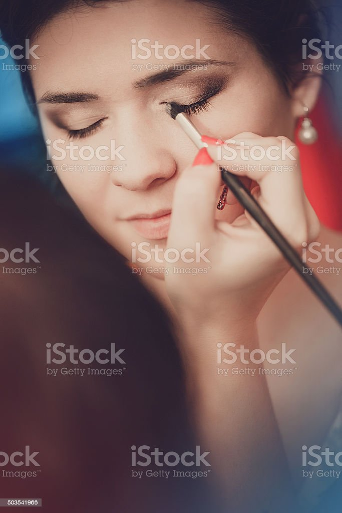 Young beautiful girl applying make-up by make-up artist close up stock photo