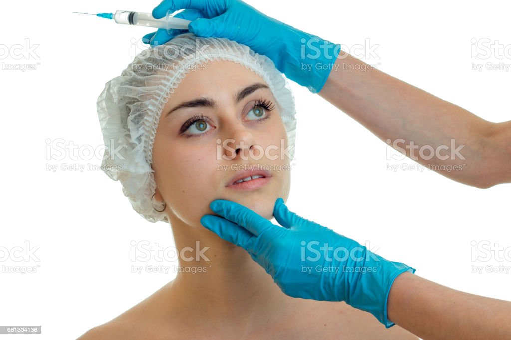 young beautiful girl came to the face shine to the beautician who gloved examines her face close-up royalty-free stock photo