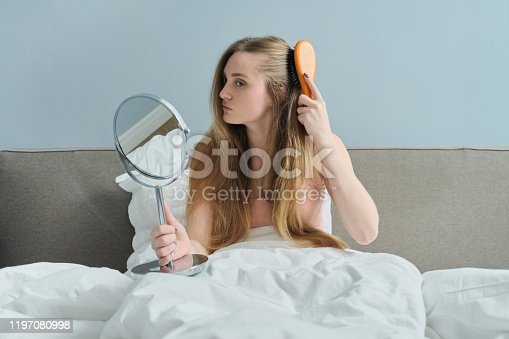 625205382 istock photo Young beautiful girl combing long hair with brush and mirror 1197080998