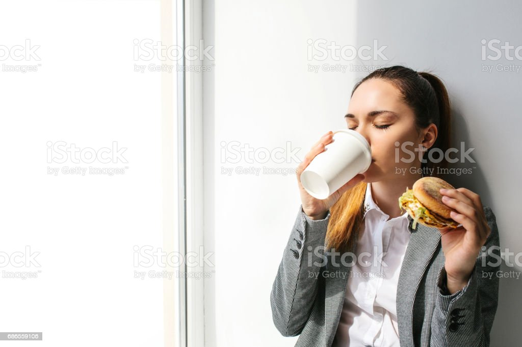 A young beautiful girl drinks coffee next to a window and eats a burger in a break between work. Fast food. royalty-free stock photo