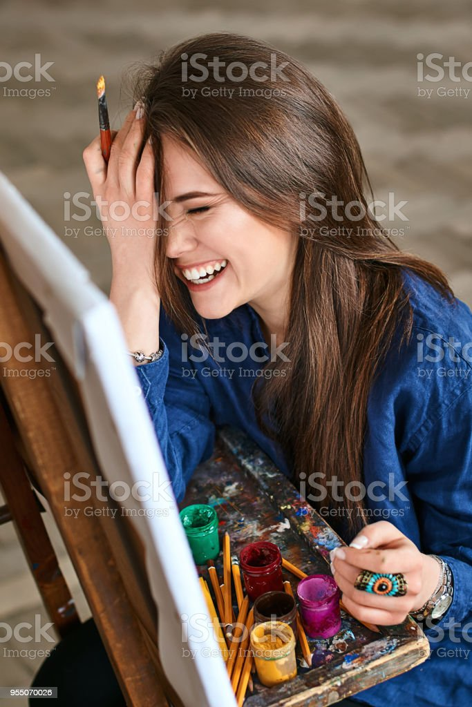Young beautiful girl, female artist painter smiling, laughing and making a facepalm gesture thinking of a new artwork with a brush in her hand stock photo