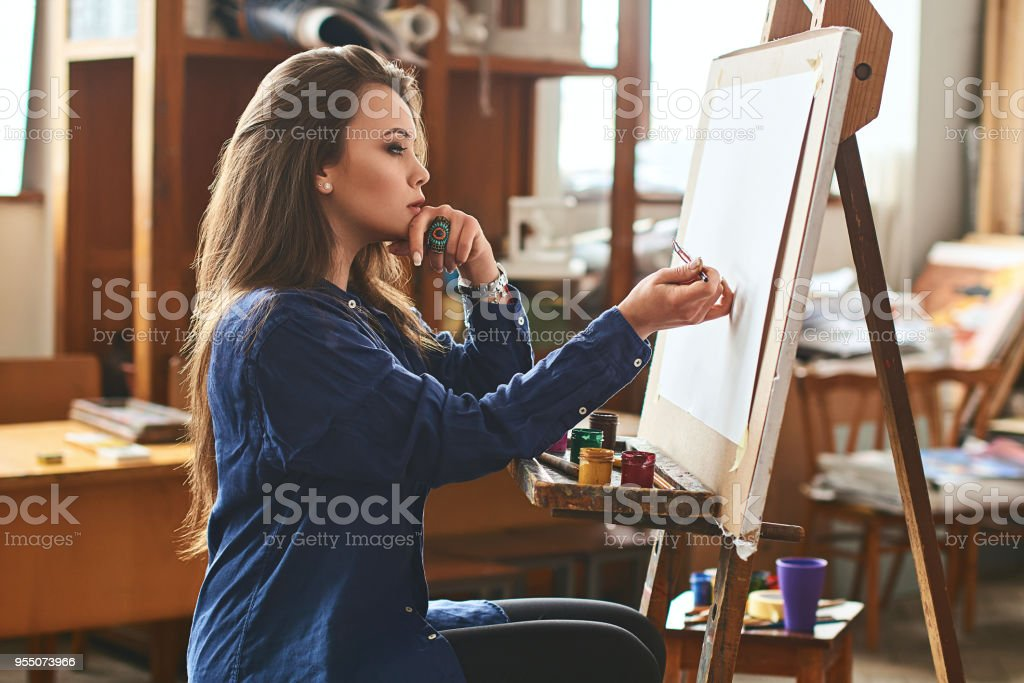 Young beautiful girl, female artist painter thinking of a new artwork idea and ready to make the first brushstroke stock photo