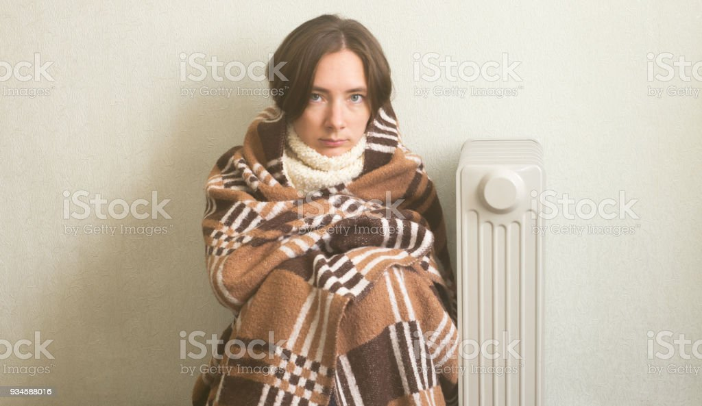 Young beautiful girl froze and warms hands near a radiator, dressed in warm woolen plaid stock photo