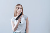 Young beautiful girl holding gun in her hands. Pistol raised up to face.