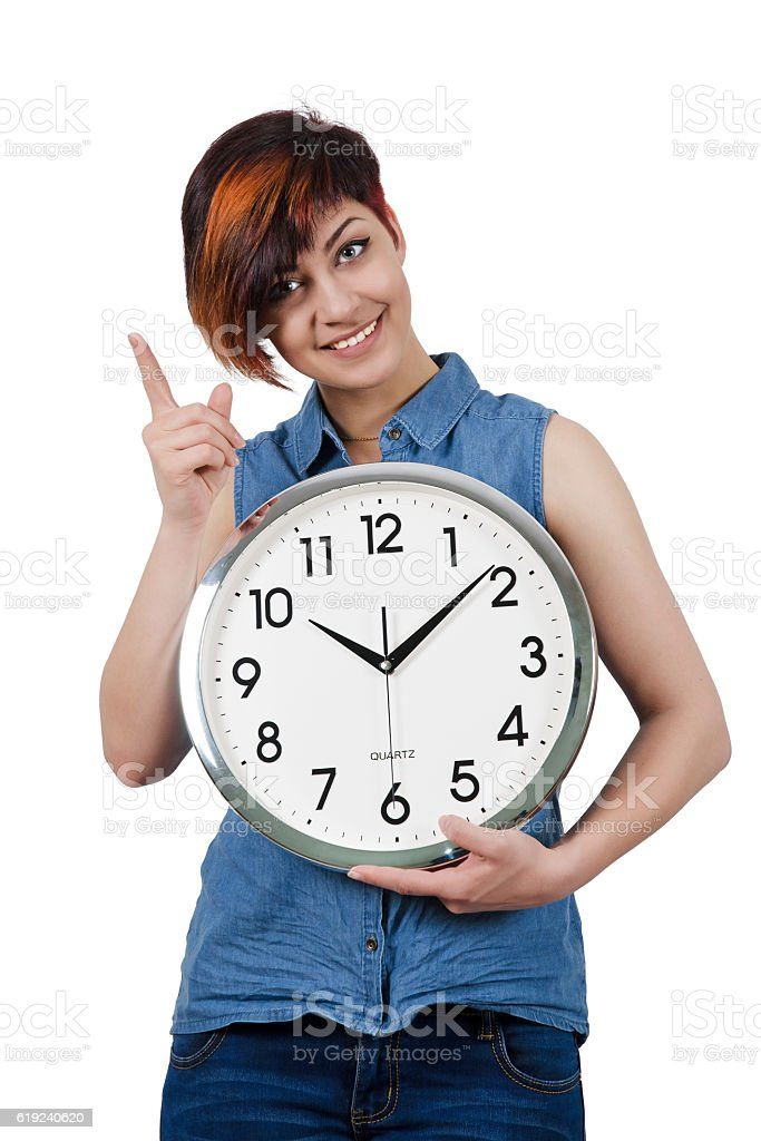 Young beautiful girl holding a large wall clock. stock photo
