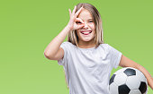 Young beautiful girl holding soccer football ball over isolated background with happy face smiling doing ok sign with hand on eye looking through fingers