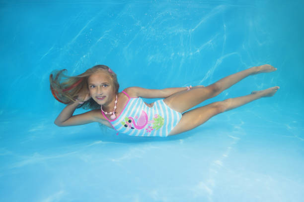 Young beautiful girl in a swimsuit is lying on the bottom of the pool stock photo
