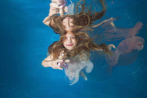 Young beautiful girl in a white dress posing underwater in the pool stock photo