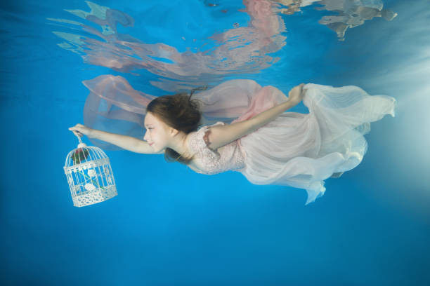 Young beautiful girl in a white dress with a rose in a birdcage swim underwater in the pool stock photo