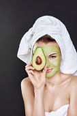 young beautiful girl in a white towel on her head with a cosmetic mask of avocado on her face.