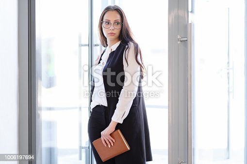638591126istockphoto A young beautiful girl in eyeglasses enters glass office door. 1006197694