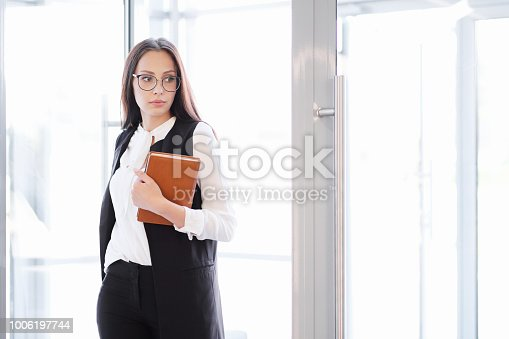 638591126istockphoto A young beautiful girl in eyeglasses enters glass office door. 1006197744