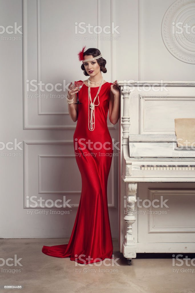 66c3f70240ca Young beautiful girl in red dress style of the 20's or 30's with glass of  martini near the piano. Vintage style beautiful woman. Old fashioned makeup  and ...