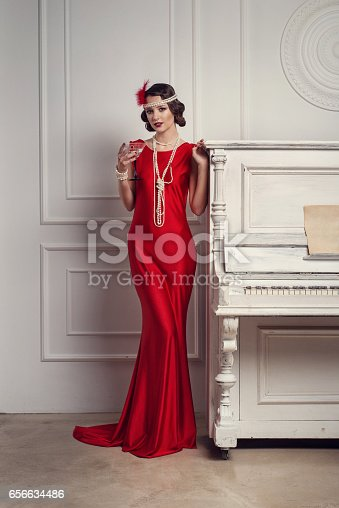 istock Young beautiful girl in red dress style of the 20's or 30's with glass of martini near the piano. Vintage style beautiful woman. Old fashioned makeup and retro finger wave hairstyle. 656634486