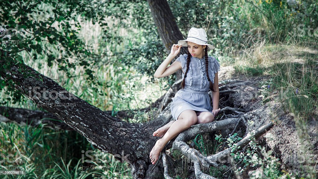 young beautiful girl in straw hat sitting on the shore royalty-free stock photo