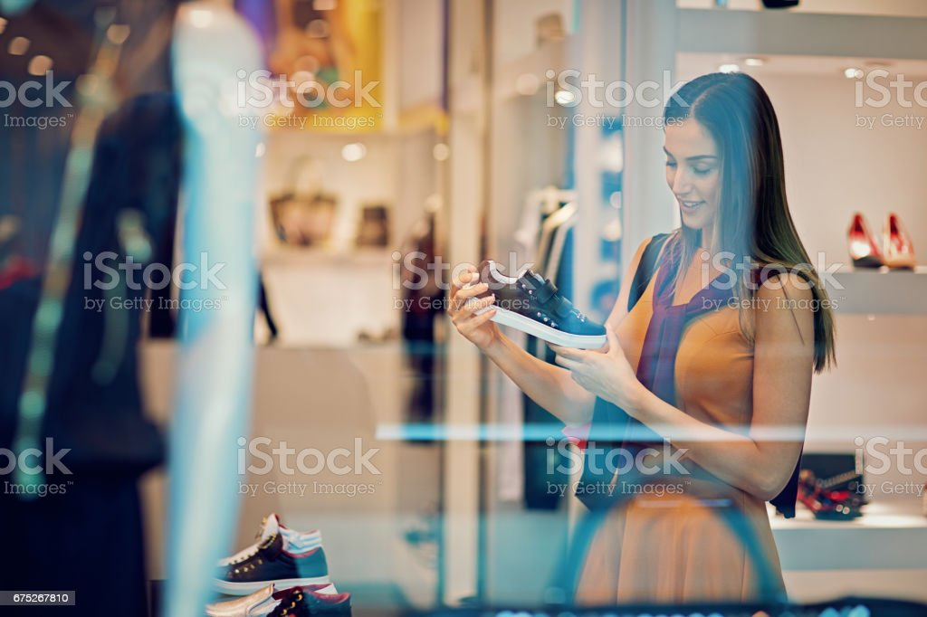 Young beautiful girl is looking shoes in the Mall stock photo