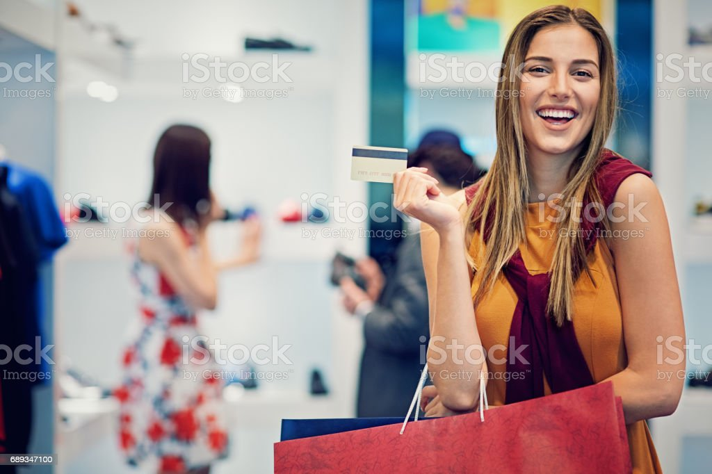 Young beautiful girl is possing with her credit card and shopping bags in the boutique stock photo
