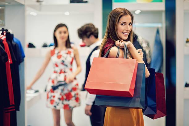 Joven hermosa chica es possing con sus bolsas de compras en una boutique - foto de stock