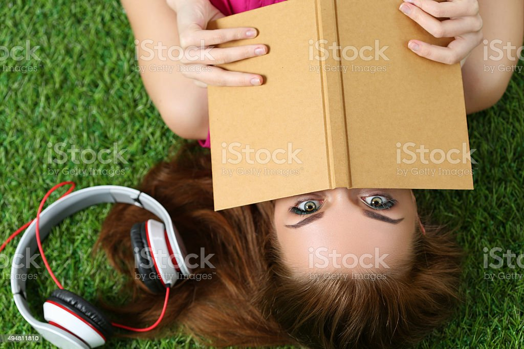 Young beautiful girl laying on the grass in park stock photo