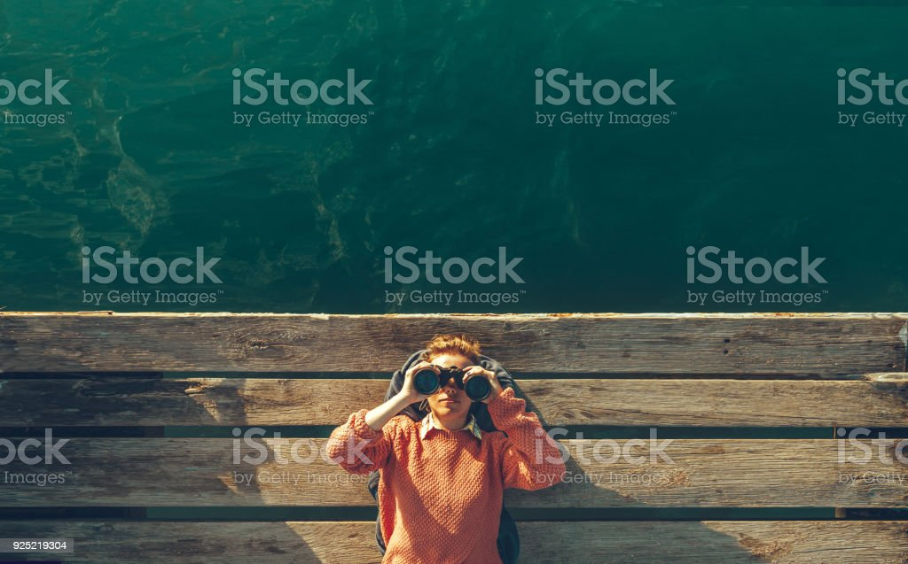Young Beautiful Girl Lies On A Pier Near The Sea And Looks Through Binoculars On Tje Sky. Travel Search Journey Concept stock photo