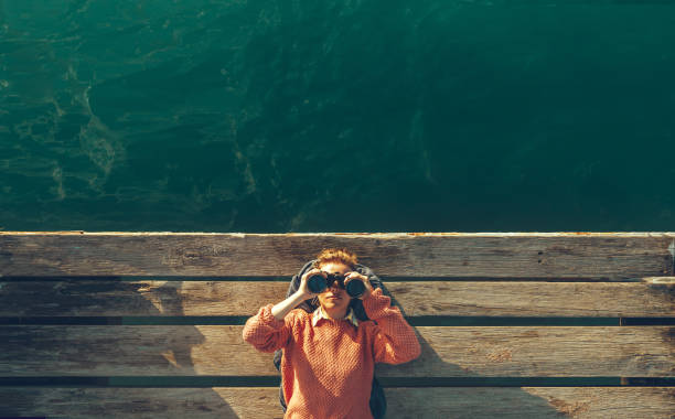 Young Beautiful Girl Lies On A Pier Near The Sea And Looks Through Binoculars On Tje Sky. Travel Search Journey Concept Young Girl In Orange Jacket Lies On A Pier Near The Sea And Looks Through Binoculars. Travel Search Journey Concept finding stock pictures, royalty-free photos & images