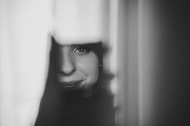 Young beautiful girl looking in the mirror and sees a reflection of lips and eyes. Woman with make-up. Black and white photo.