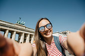 istock Young beautiful girl makes selfie or takes pictures of sights. 1150083595