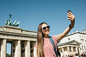 istock Young beautiful girl makes selfie or takes pictures of sights. 1150084197