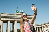 istock Young beautiful girl makes selfie or takes pictures of sights. 1150084736