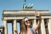 istock Young beautiful girl makes selfie or takes pictures of sights. 1150086316