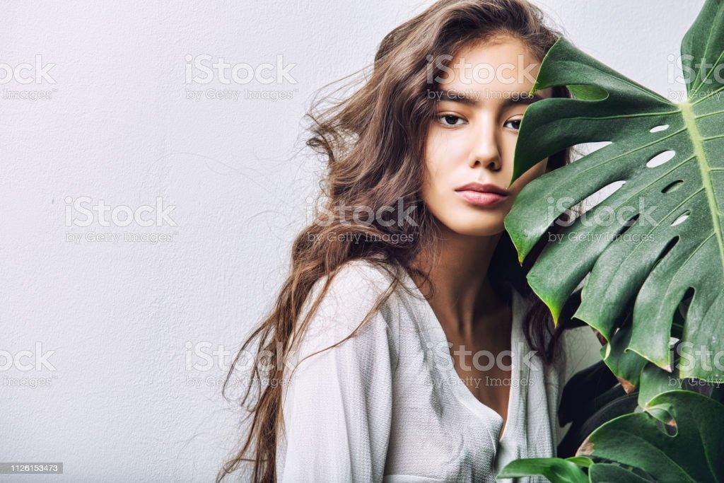 Morena asiática de niña hermosa modelo con el pelo largo, posando en el estudio con plantas tropicales sobre fondo aislado foto de stock libre de derechos