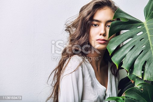 istock Young beautiful girl model Asian brunette with long hair posing in Studio with tropical plant on isolated background 1126153473