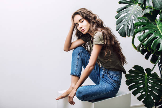 Young beautiful girl model Asian brunette with long hair posing in Studio with tropical plant on isolated background stock photo