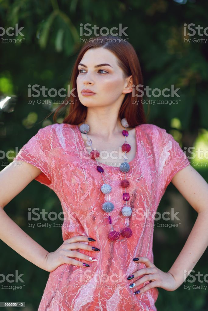 6da9590e3206da Hermosa niña posando en ropa de diseñador en un transparente vestido hecho  de lana merino rosa