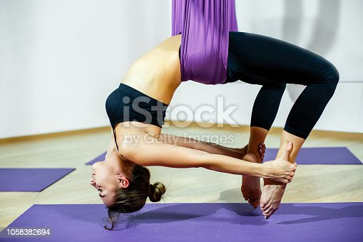 istock Young beautiful girl practicing aerial yoga in gym. 1058382694