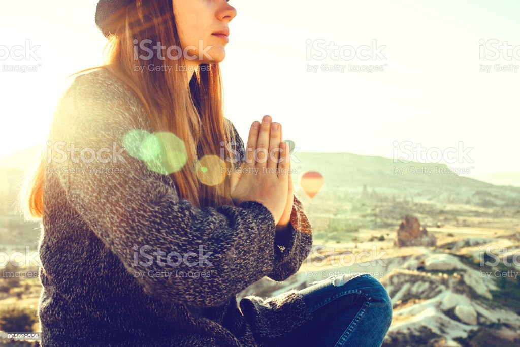 Young beautiful girl practicing yoga at the top of a mountain in Cappadocia at sunrise. Practices of relaxation. stock photo
