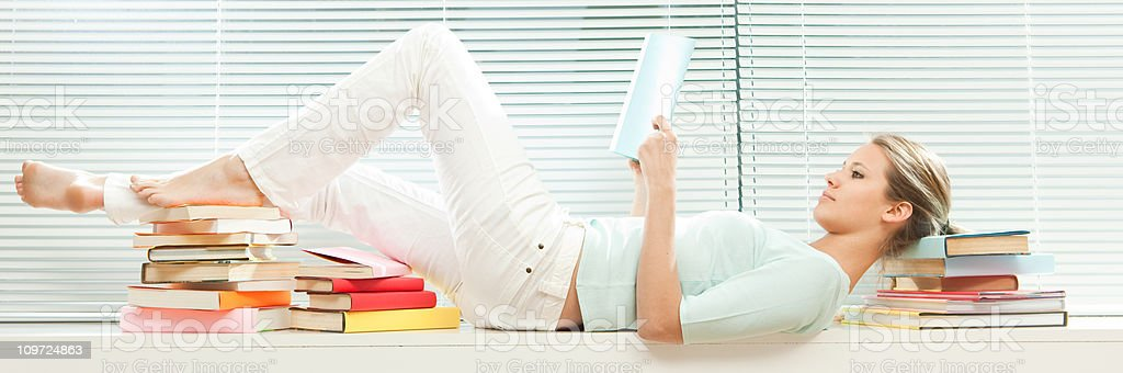Young beautiful girl reads book lying down royalty-free stock photo