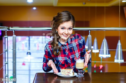 young beautiful girl in cafe shows to cup of mokachino and cake