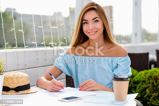 istock Young beautiful girl signs contract with pen table in summer cafe restaurant. Concept conclusion of transaction agreement, painting, notarized document. Emotions of joy smile and pleasure from work. 1133691594