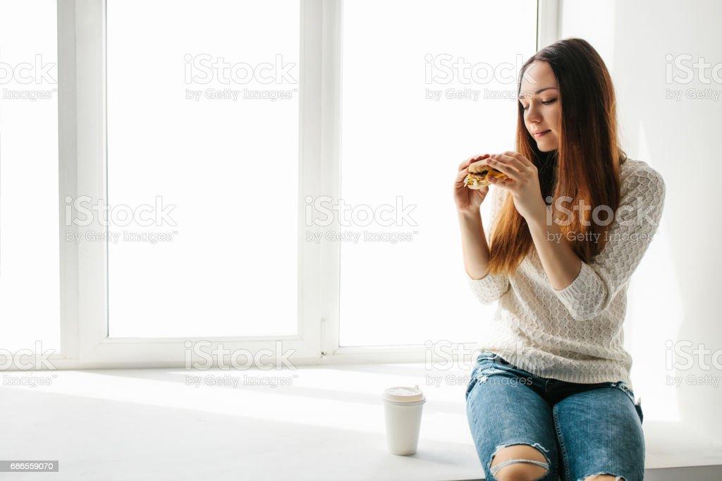 Une belle jeune fille est assis sur une fenêtre et mange un hamburger avec du café. Collation rapide. Restauration rapide. photo libre de droits