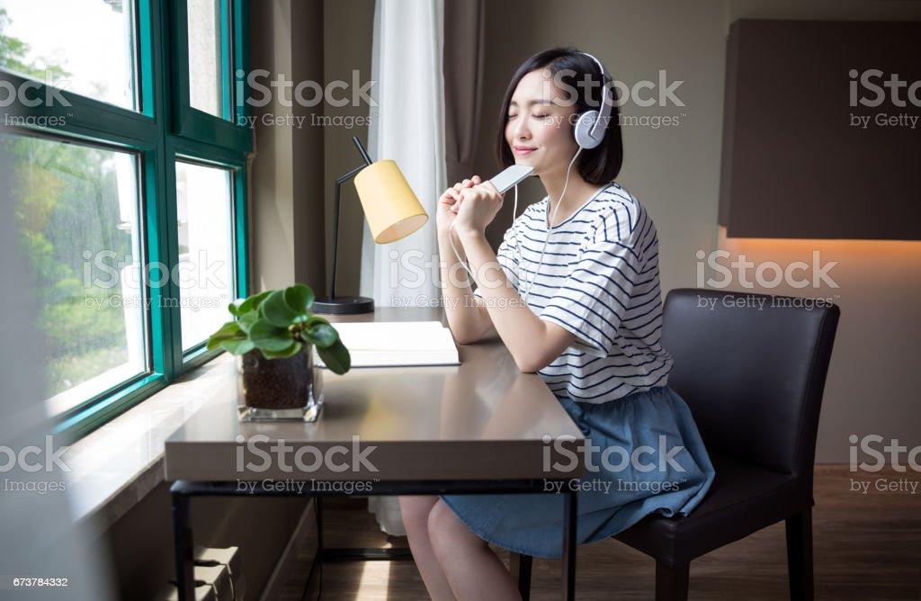 Jeune fille belle assise près de la fenêtre écrire quelque chose à la maison photo libre de droits